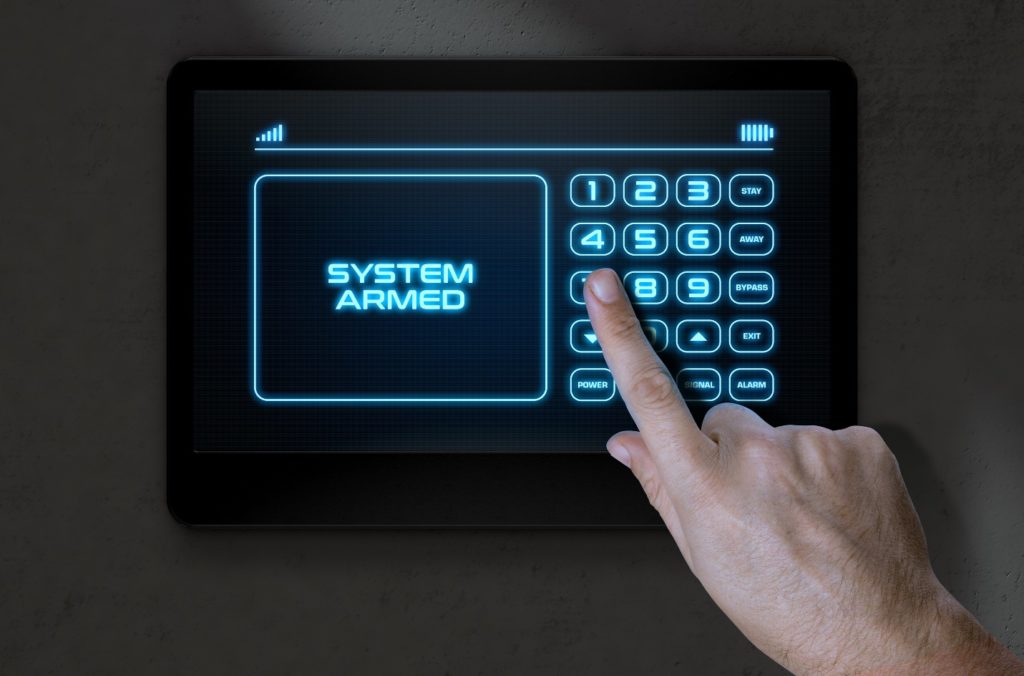 A male hand pressing the screen of a home security control panel with words that read system armed