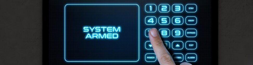 Une main masculine appuyant sur l'écran d'un panneau de contrôle de sécurité à domicile avec des mots qui lisent le système armé